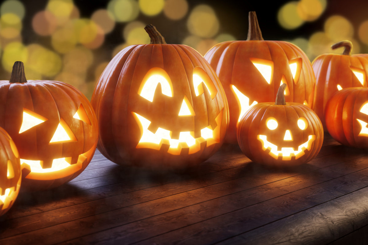 A family of Jack O' lanterns sitting on a dark wooden bench, with bokeh lights in the background.